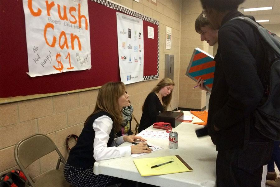 Ms. Bode and FCCLA staff sell crush cans during lunch.