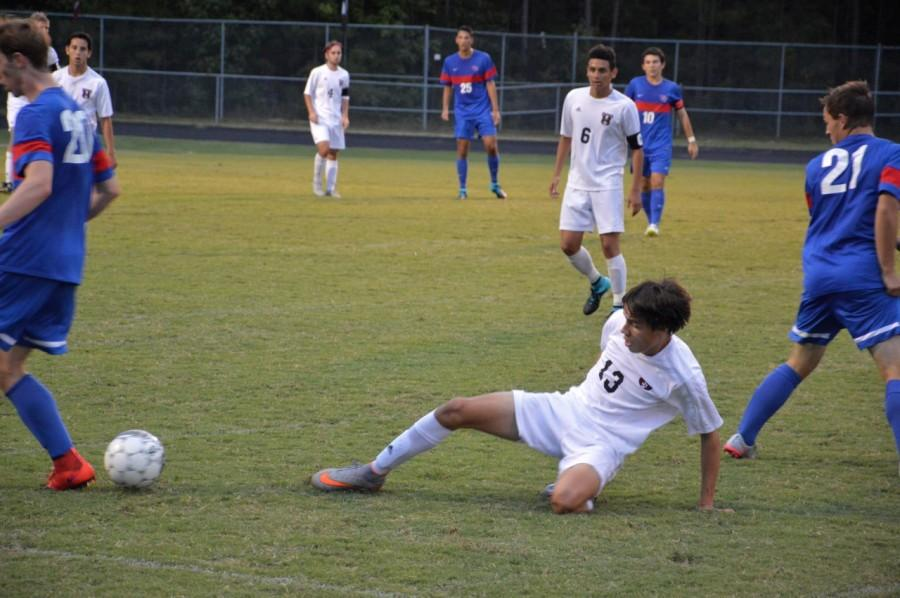 Junior, Marcus Shenker-Tauris, attempts to slide tackle an opposing Wake Forest High School soccer player.