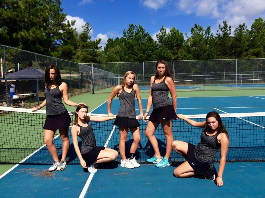 Seniors on the women's tennis team pose for the camera before a match.