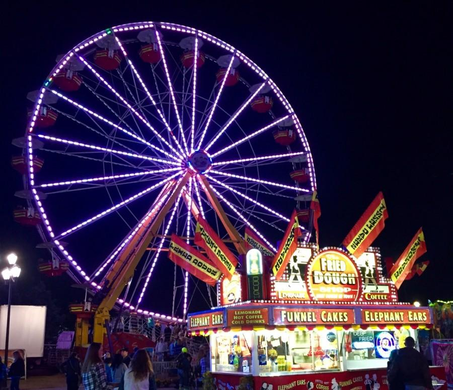 The ferris wheel at the State fair stands tall among the other attractions.