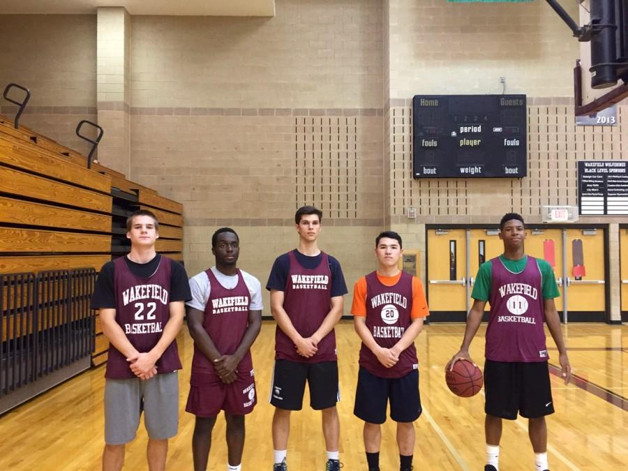 A few players on the mens basketball team pose for a photo before practice.