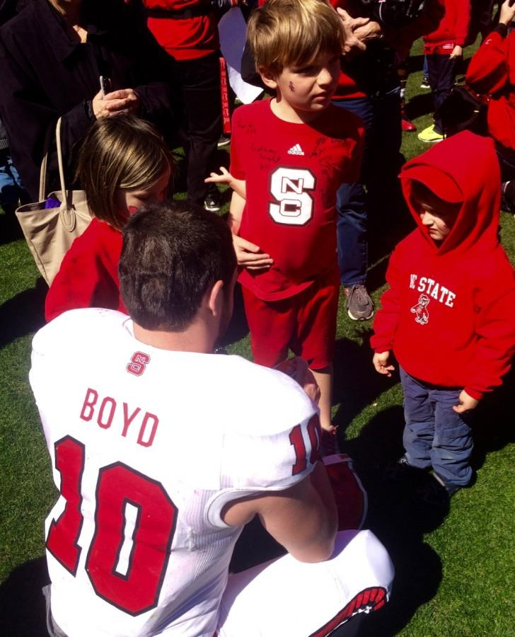 Heath Boyd signs autographs for kids at NC State's spring football game.