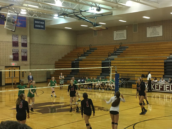 Wolverines anticipate a serve from their opponent, Leesville.