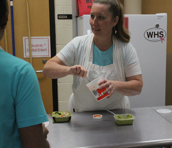 Foods Teacher, Ms. Hayden serves sauce as a part of a cooking lesson to her students.