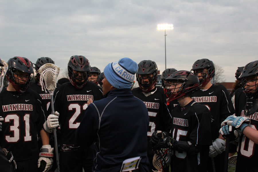 Mr. Cummings talking to the lacrosse team during a timeout