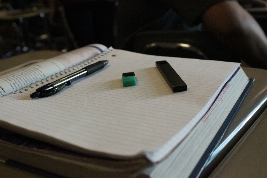 A Juul Device (right) and a Juulpod (center) look undetectable on an average student's notebook.