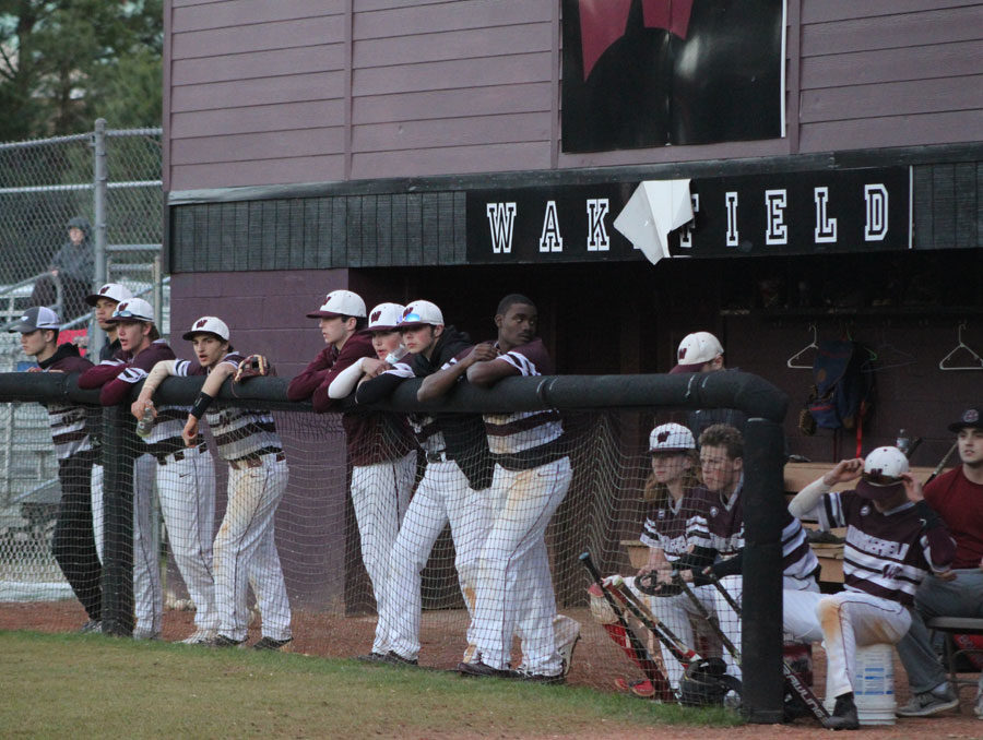 The Wakefield Men's Baseball team watcyes the game from the dugout.