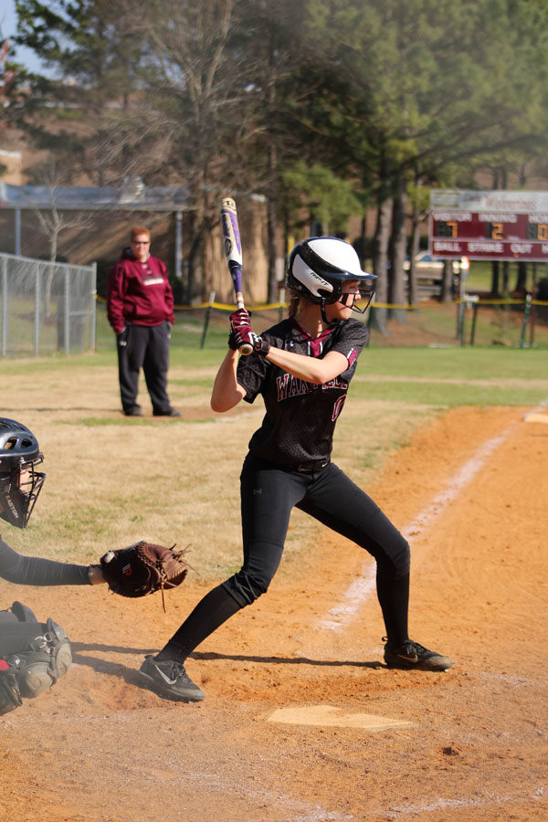 A softball player getting ready to swing the bat.
