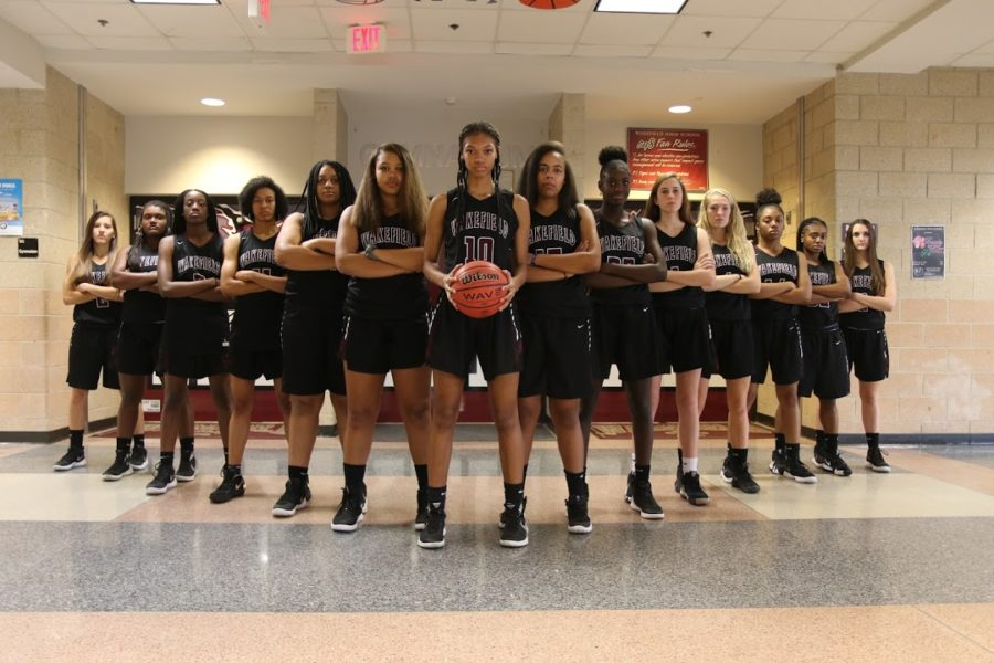 The varsity womens basketball players pose as a team.