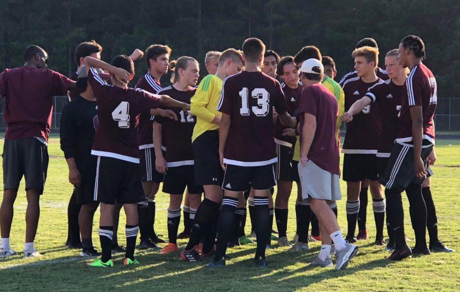 Mens soccer team huddles up before taking on Green Hope.