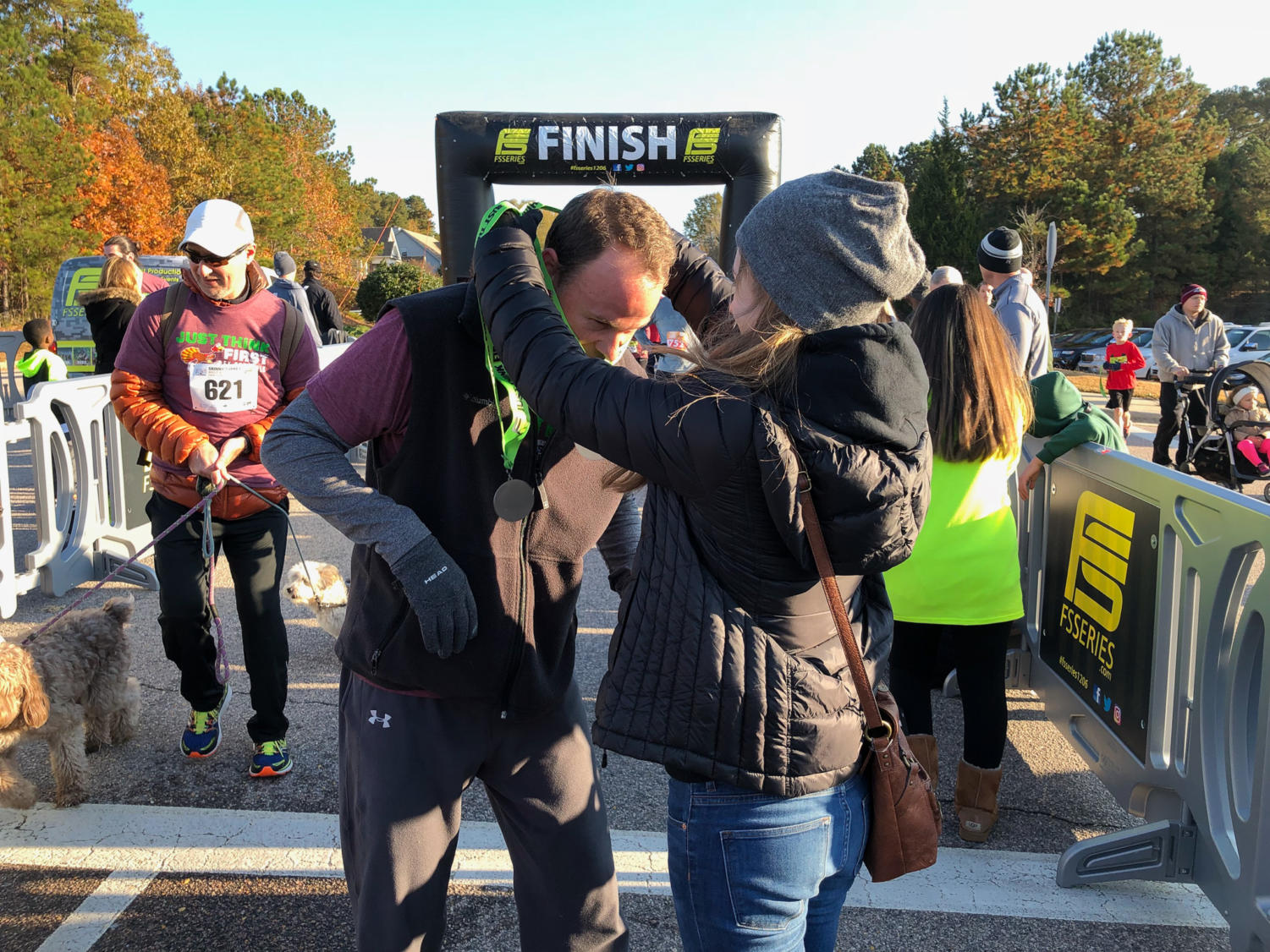 Junior Sky Ashforth, passes out a medal to her dad at the Skinny Turkey Run