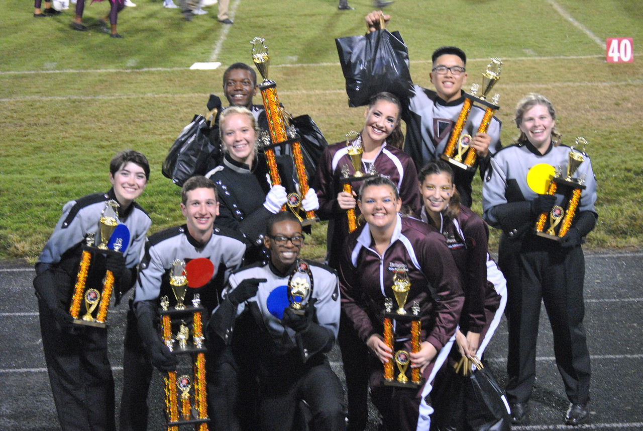 Marching band and color guard student leaders pose with their trophies.