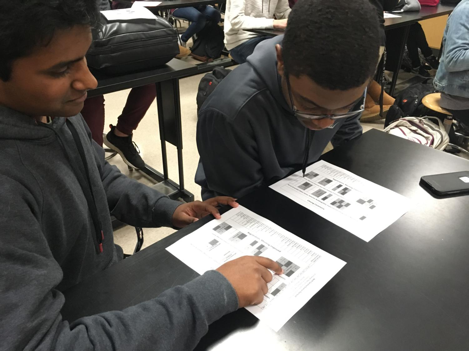 Senior Michael Mathew and Sophomore Emanuel Smith study Science Olympiad schedule.