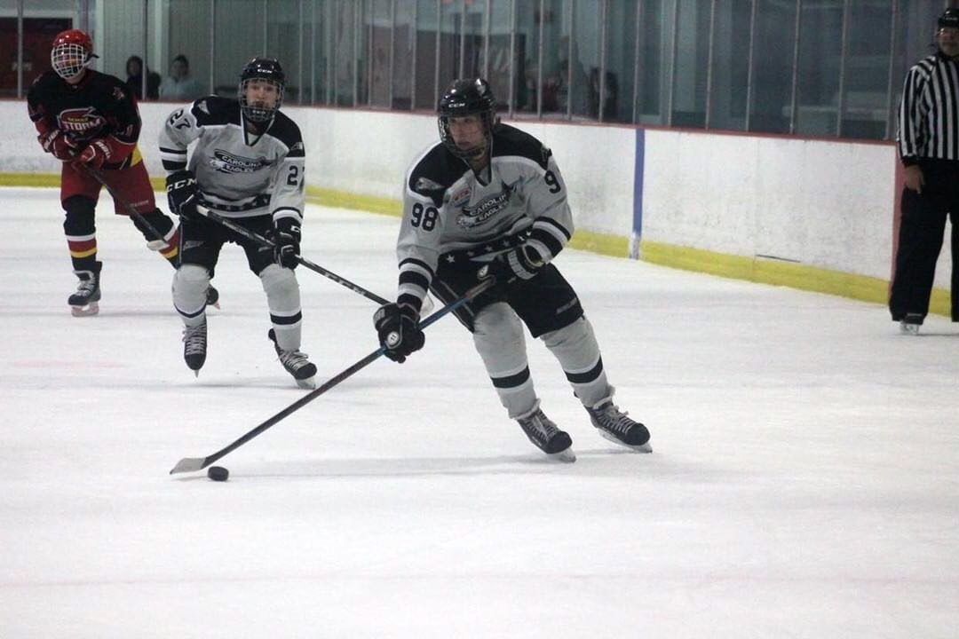 Student, Andrew Robbins, handles the puck for the Eagles hockey team.