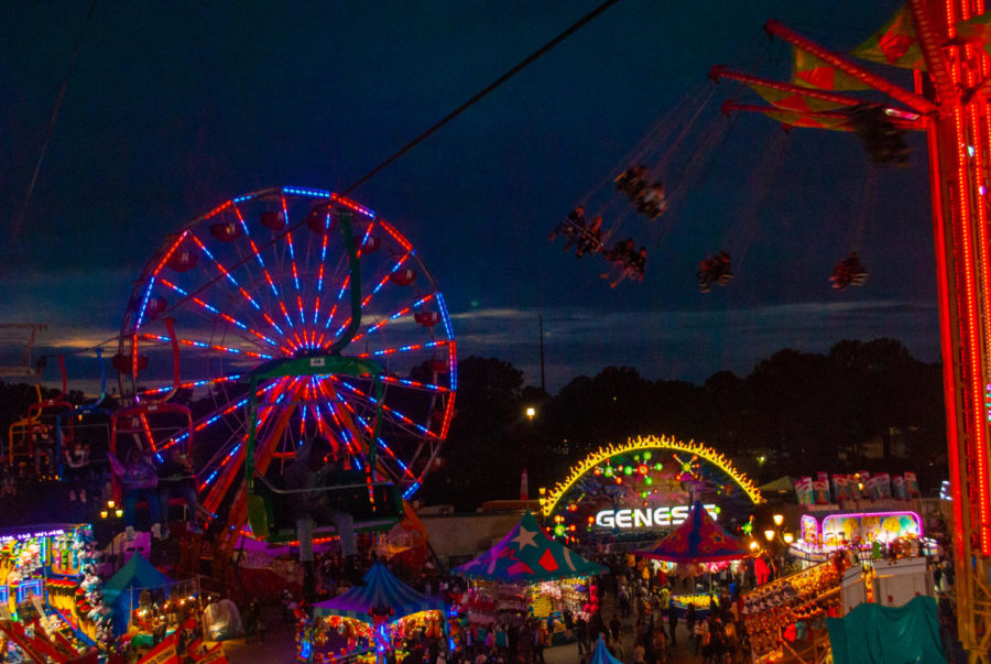 The fair's colored lights shine on a cloudy night.