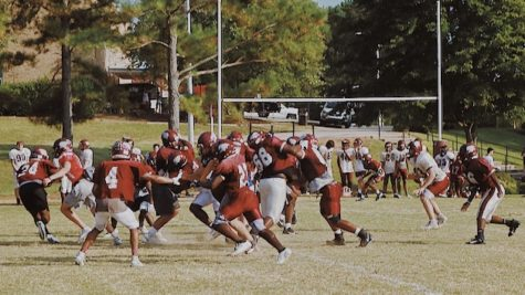 The varsity football team practices their plays for their weekly games.