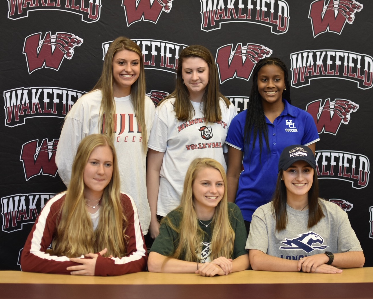 Wakefield's signees smile for a picture after signing with their future universities.