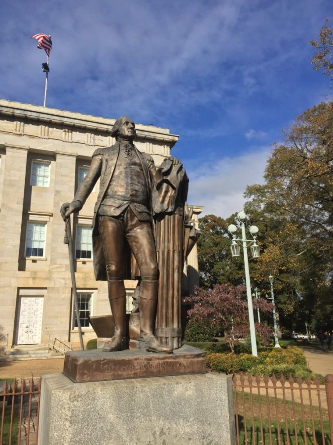 Fall leaves surround a statue of George Washington in front of the Raleigh Capitol Building.