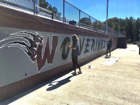 Mira Valentino and Angelina Ramirez finish the fine details of the Wolverine mural.