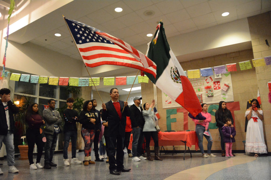 The American and Mexican flag are waved in front of a group of dancers.