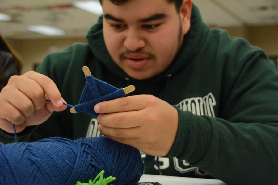 A student concentrates on his artwork.