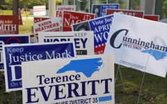 Clusters of campaign signs for local elections sit on the side of an Early Voting building.