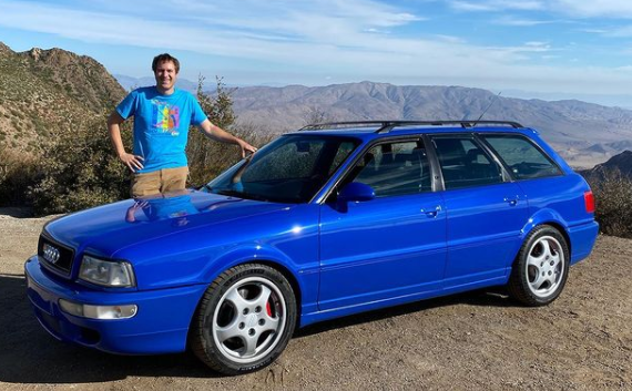 Youtuber Doug DeMuro stands next to his newly acquired Audi RS2 Avant.
