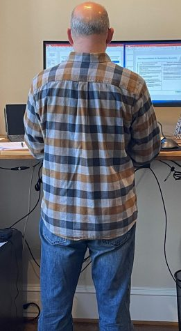 A man stands in front of his computer wearing a collared shirt and jeans.