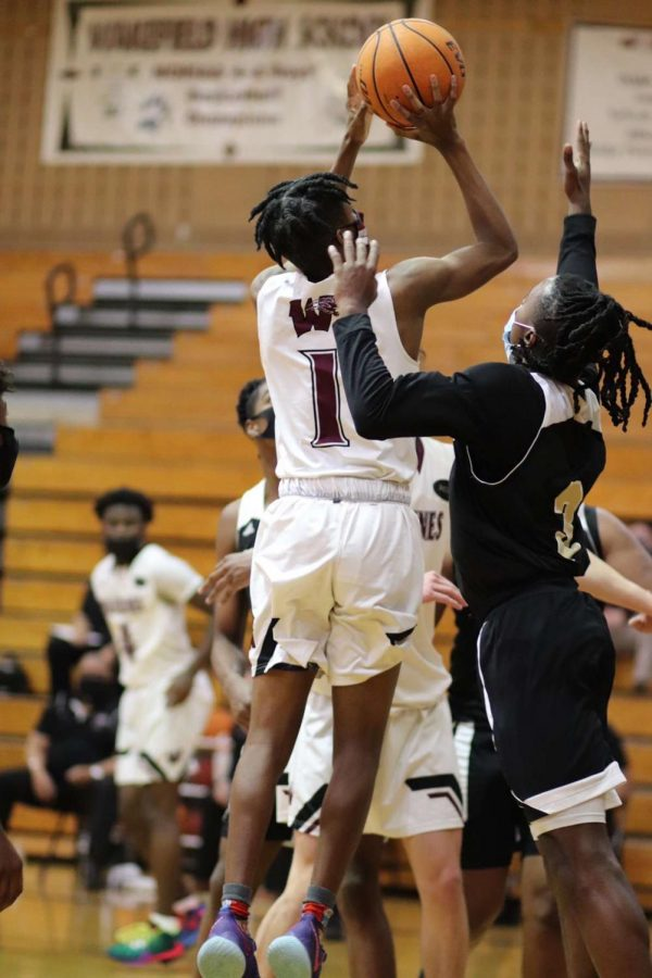 Sophomore point guard, Elijah Preddy shoots over a Knightdale player.
