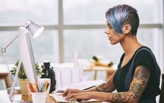 Women working at desk with tattoos and colored hair.